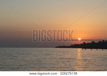 Golden Sunset At Sea. The Sun Shines At Sunset Through The Cloud. The Sunshine Is Blazing On The Sea