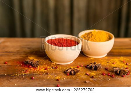 Close Up Two Bowls Filled With Red Paprika And Yellow Turmeric Powder On Dark Wooden Table Covered W