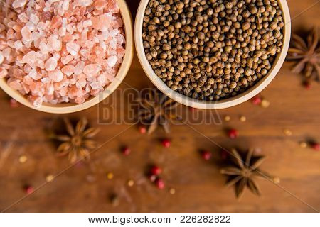 Pink Himalayan Salt And Coriander Seeds In White Bowls On Wooden Surface Covered With Anise And Red