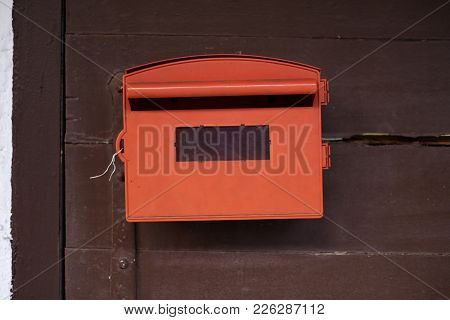 Red Mailbox With Brown Wood Background. Concept Of Paper Correspondence In Modern World