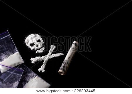 Drug Dependence Kills. A Line Of Cocaine In The Form Of A Skull And A Roll Of A Dollar, Sachets With