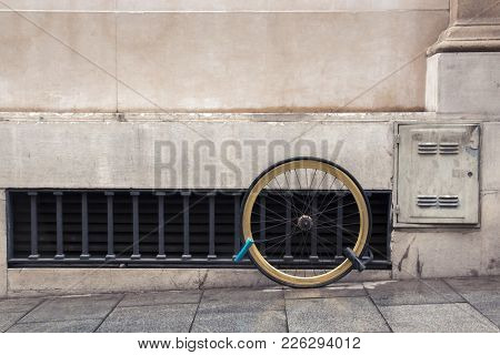 One Wheel Of A Bicycle Chained By Two Locks To The Facade Of The House, The Concept Of The Problem O