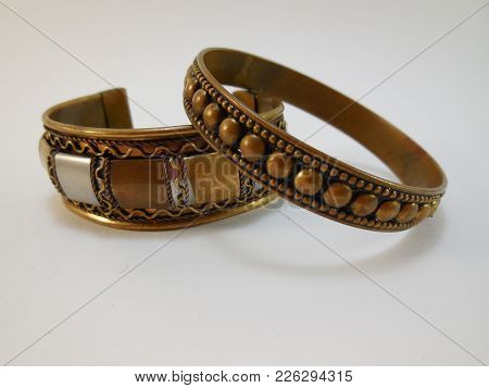 Two Indian Bracelets Made Of Brass Lie Side By Side On A White Background