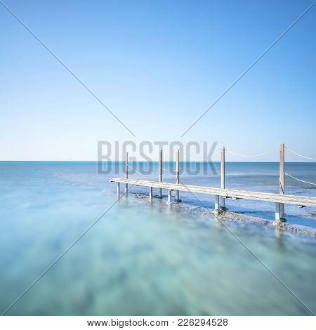 Wooden Footbridge Or Catwalk And Banister On Ocean Water. Long Exposure Photography.