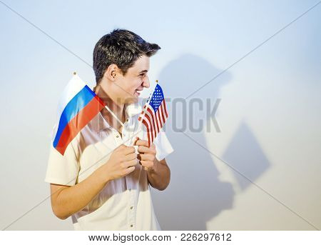 Adorable Brunette Guy Holding The Flag Of The Usa And Russia