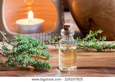 A Bottle Of Thyme Essential Oil With Fresh Thyme Twigs And An Aroma Lamp