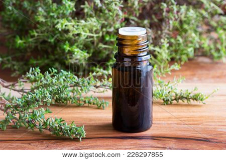 A Brown Bottle Of Thyme Essential Oil With Fresh Thyme Twigs On A Wooden Table
