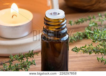 A Dark Bottle Of Thyme Essential Oil With Fresh Thyme Twigs And A Candle In The Background