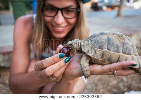 Happy young woman feeding turtle with cherry