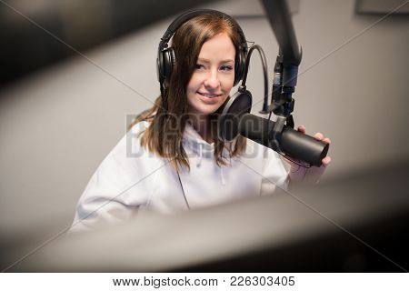Young Female Host Using Headphones And Microphone While Looking Away In Radio Studio