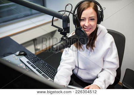 High Angle View Of Young Female Jockey Smiling While Communicating On Microphone In Radio Studio