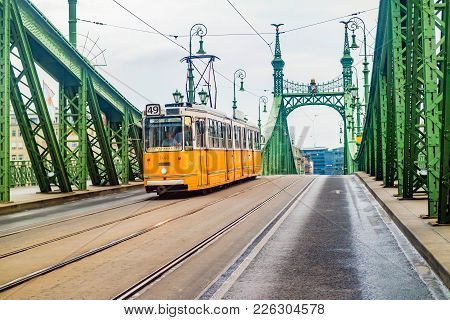 Budapest, Hungary - June, 2017: Liberty Bridge Or Freedom Bridge And Yellow Tram In Budapest, Hungar