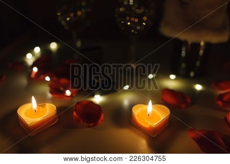 Close Up View Of A Romantic Dinner Table With Glasses Of Wine, Roses, Candles And A Engagement Ring.