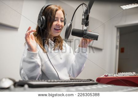 Happy Young Female Host Communicating On Microphone In Radio Studio