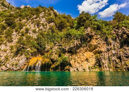 Adorable waterfall on the wall of the gorge. The azure waters of the river flow between the steep walls of Limestone Canyon Verdon. Concept of ecological and active tourism