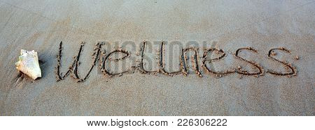 Word Wellness Written On The Sand Near The Sea. Wellness Concept Written On Sand.