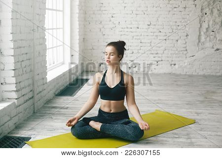 Atractive Young Caucasian Woman Working Out At Home, Doing Yoga Exercise On Green Mat, Sitting In Lo