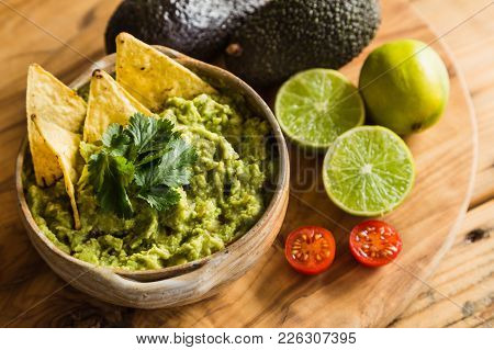 Tortilla Chips In A Bowl Of Guacamole Dip With Avocado Limes And Cherry Tomato Ingredients
