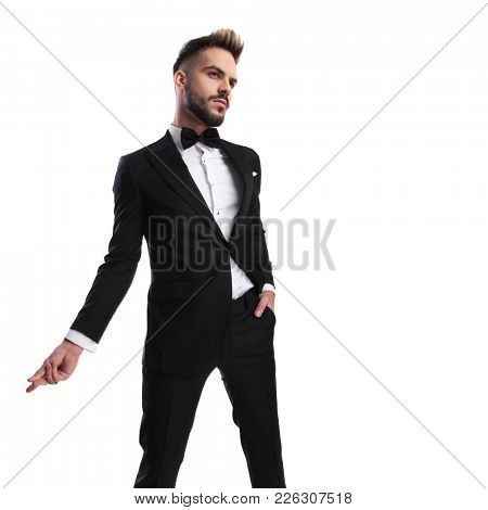 wide angle side view of an elegant man in tuxedo snapping his fingers on white background