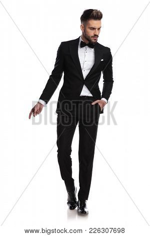 young handsome man in tuxedo is snapping fingers and looks to side on white background