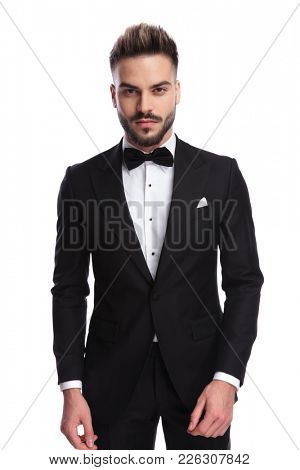portrait of a young handsome elegant man in tuxedo standing on white background