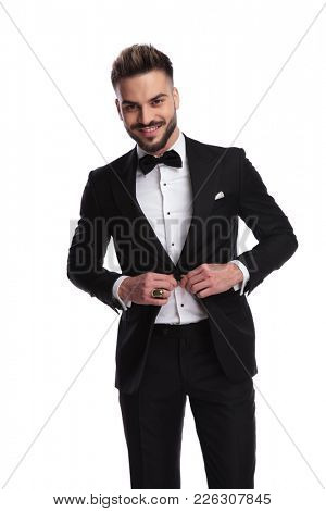elegant man unbuttoning his tuxedo and laughs on white background