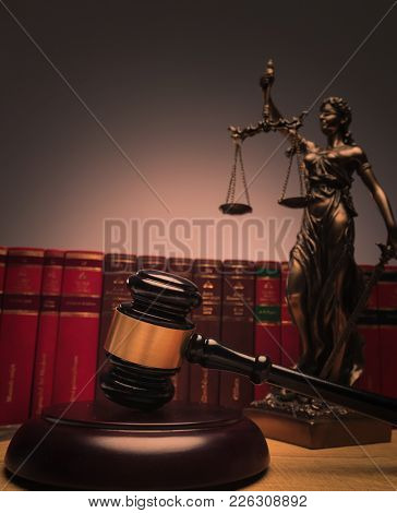 judge's gavel with justice statue and law books in the background