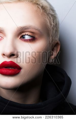 Portrait Of A Young Blonde With Short Hair And Lush Lips.