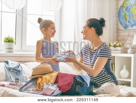 Go on an adventure! Happy family preparing for the journey. Mom and daughter are packing suitcases for the trip.