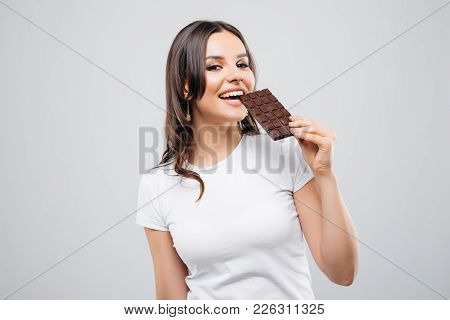 Portrait Of A Brunette Young Woman Biting Chocolate Isolated On White Background