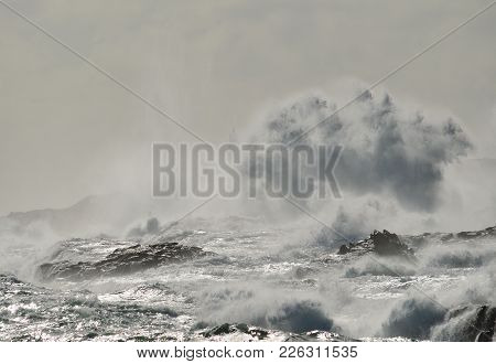 Rough Sea On The Coast, Big Wave When Breaking And Blurred Silhouette Of Lighthouse In The Backgroun