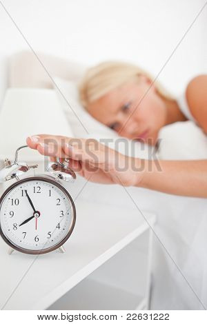Portrait of an unhappy woman switching off her alarm clock in her bedroom