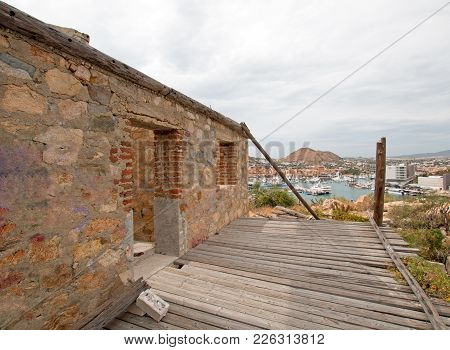 Abandoned Brick And Stone Building On Hill Above Cabo San Lucas Marina And Harbor In Baja California