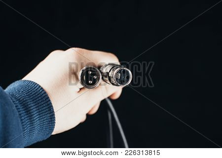Xlr, Connector With Wires In Hand On Dark Background In Studio