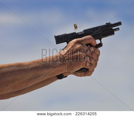 Smoke And And Brass Leaving A Handgun A Split Second After It Is Shot