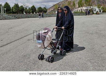Tehran, Iran - April 28, 2017: Two Iranian Women In Black Hijab And Sunglasses Are Walking Along The
