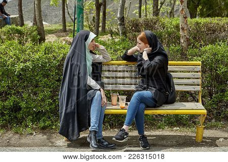 Tehran, Iran - April 28, 2017: Two Iranian Women In Hijabs Sit On A Bench In A Park With Drinks And