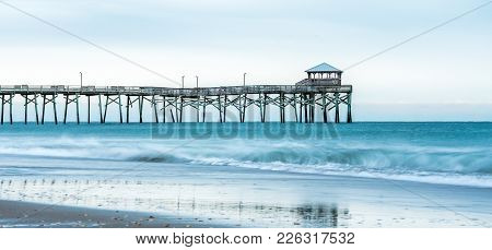 Sunrise With The Atlantic Beach Pier In The Background With Sand, Ocean, Waves And Blue Clouds