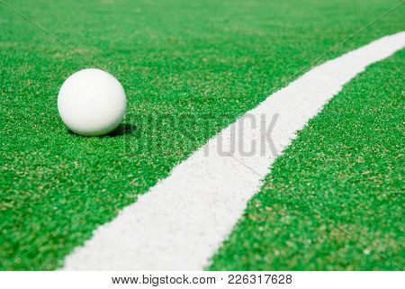 Green artificial grass hockey field with lines and ball