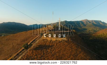 The Sign Of The City Of Coron Is On A Hill, A Famous Tourist Place. Aerial View: Catholic Cross On A