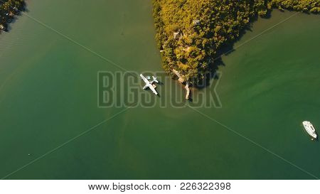 Aerial View: White Seaplane Parked In The Sea Bay Of The Tropical Island. Hydroplane In The Lagoon A