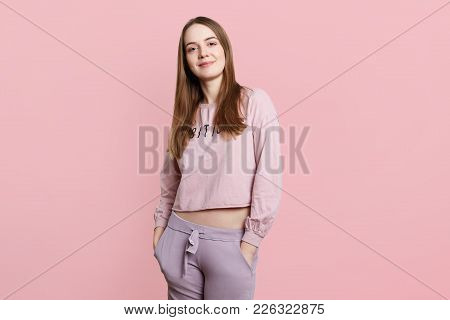 Slim Sporty Female Model Wears Casual Sport Clothes, Keeps Hands In Pockets, Looks Directly Into Cam