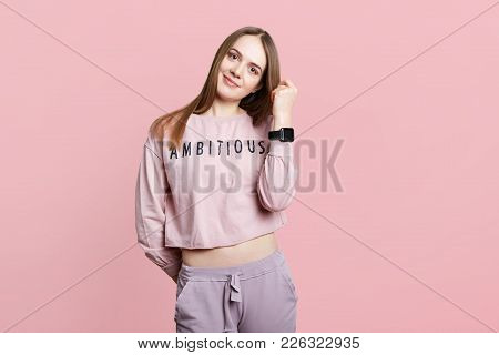 Indoor Shot Of Pretty Female Dressed In Loose Sweater And Trousers, Has Wristwatch On Arm, Pleased T