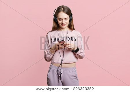 Indoor Shot Of Brunette Woman Listens Audio Book In Headphones, Types Messages On Cell Phone, Connec