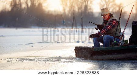 Happy elderly man on winter fishing on the frozen lake