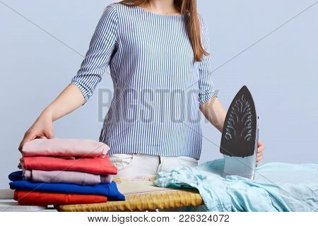 Unrecognizable Female In Blouse Stands At Iron Board Surrounded With Pile Of Laundry, Going To Iron,