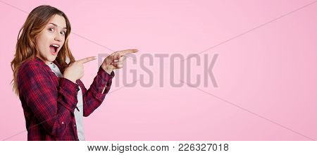 Excited Beautiful Woman Stands Sideways, Wears Chemise, Points With Fore Fingers Aside At Blank Copy