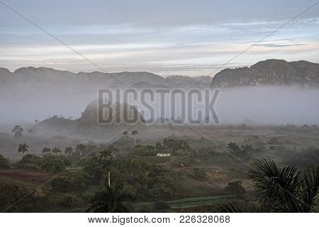 Vinales Valley In Cuba In Morning Mist And Surrounded By Mountains