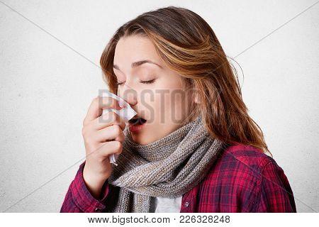 Sideways Portrait Of Young Woman Has Allergic Rhinitis, Sneezes Into Napkin, Has Headache, Wears Sca