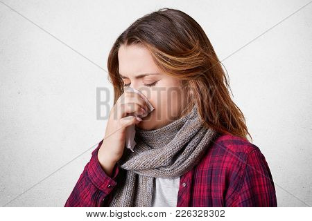 Unhappy Frustrated Female Model Got Sick Because Of Cold Winter Weather, Sneezes And Has Running Nos